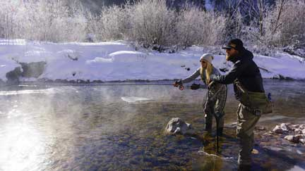 Fisherman casting while a fly fishing guide looks on. Both are wading in Gore Creek near Vail, CO.