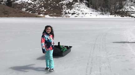Young child pulls a sled on a frozen lake near Eagle, CO.